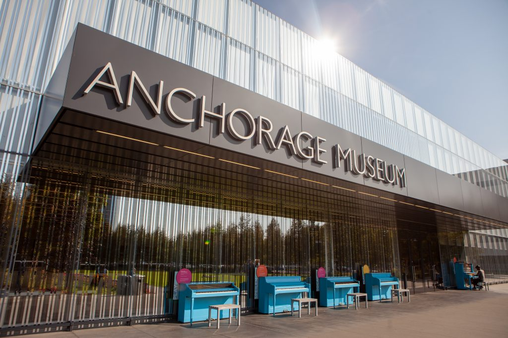 Anchorage Museum building with pianos out front