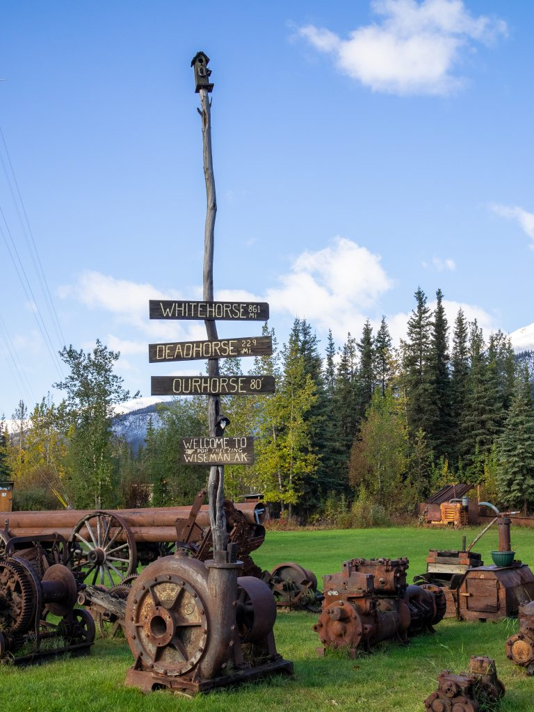wooden post with painted mileage signs shows this secret Alaska stop is far off the grid
