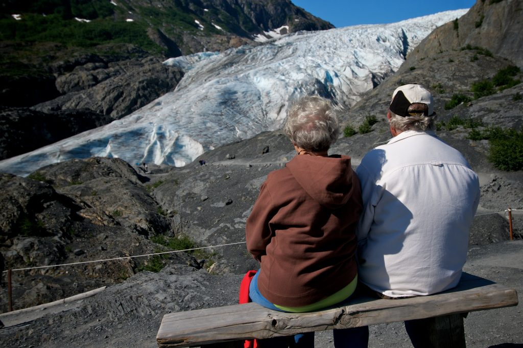 Exit Glacier hikers enjoy the view and sit on a bench