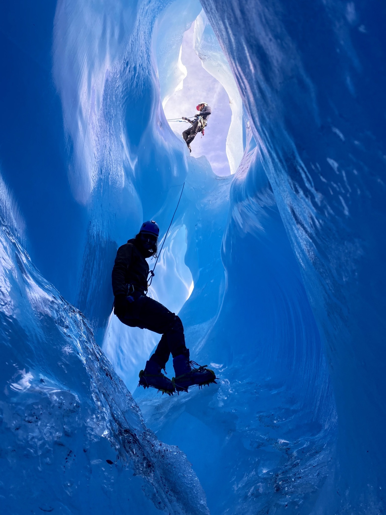 Two explorers descend into an icy glacier roped up and wearing crampons