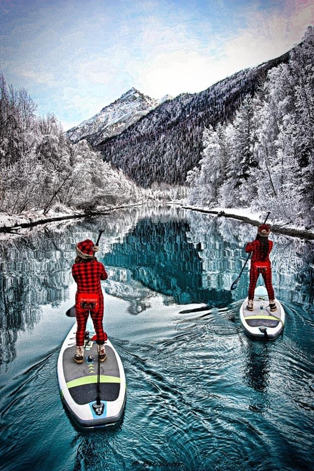 Two women in red onesies paddleboard on a river surrounded by snowy trees