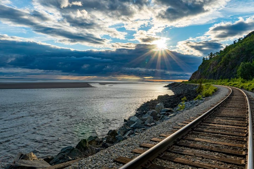 Sun sets behind clouds over water and winding train tracks on the shore