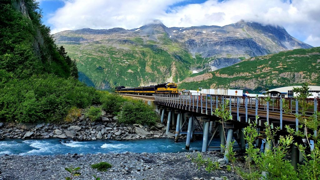 Alaska Railroad train crossing a bridge over a river with scenic mountains behind