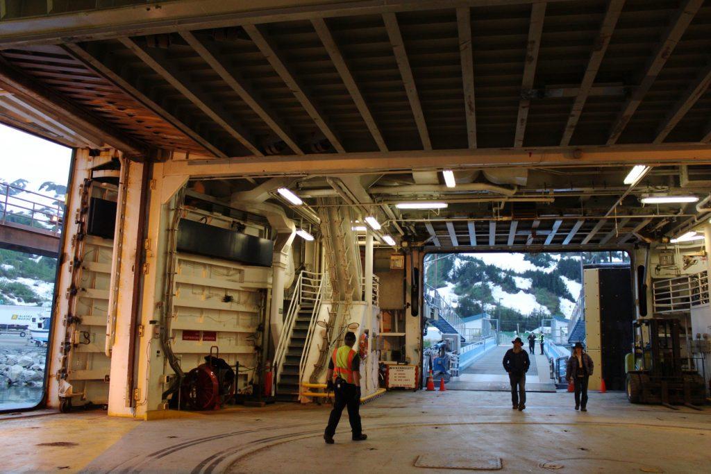 People walk aboard the cargo area of an Alaska ferry