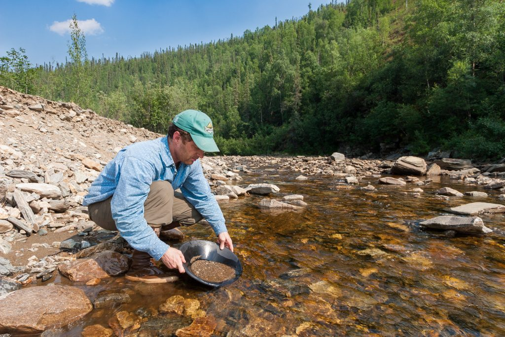Man in hat pans for gold in a stream