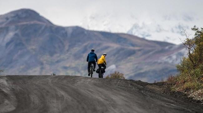 Two cyclists biking on Denali Park Road