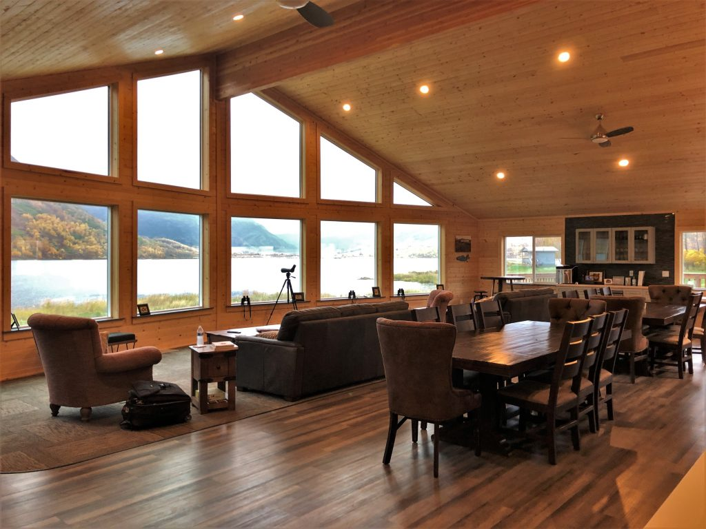 A spacious room with floor to ceiling windows and lots of wood