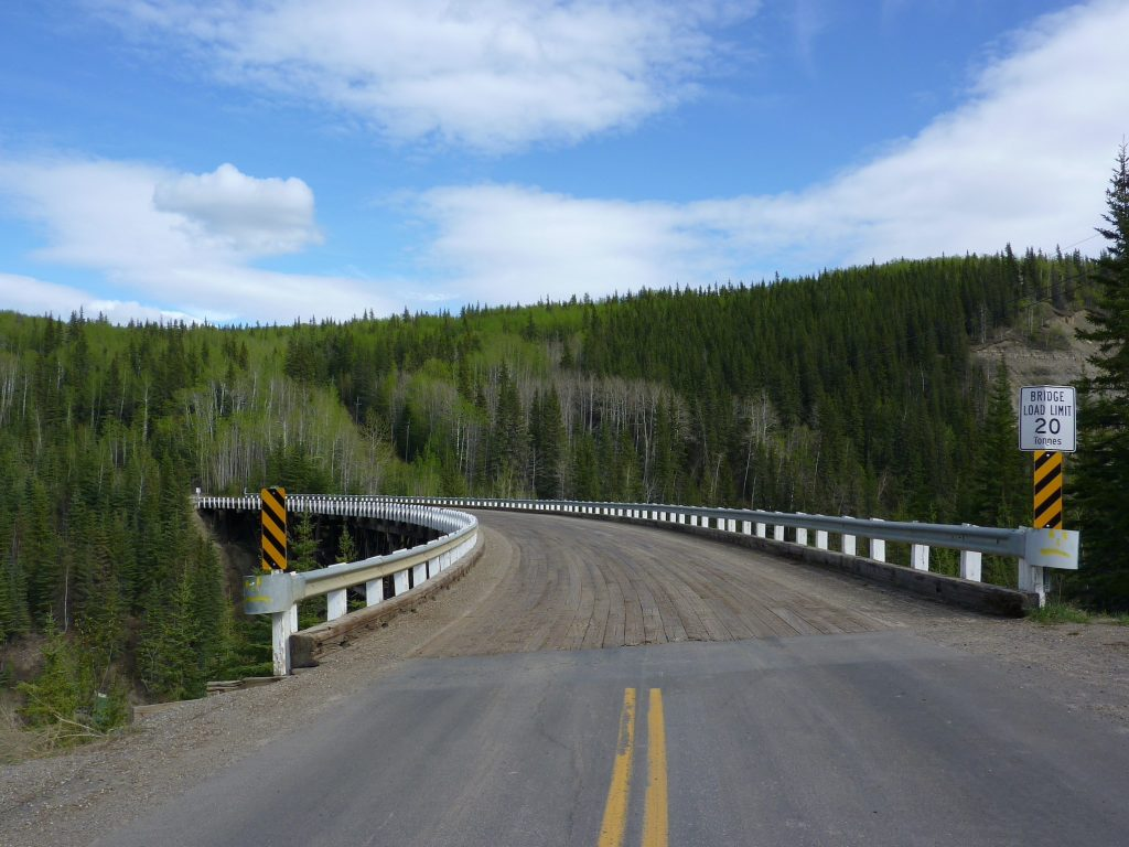 road leading to a curved wooden bridge